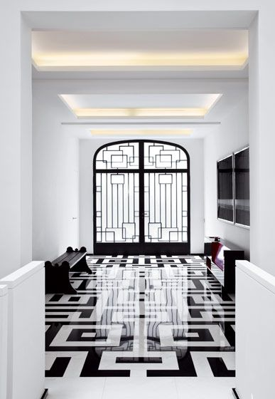 The geometric marble floor is patterned to reflect the custom-designed metal door by Pierre Yovanovitch.