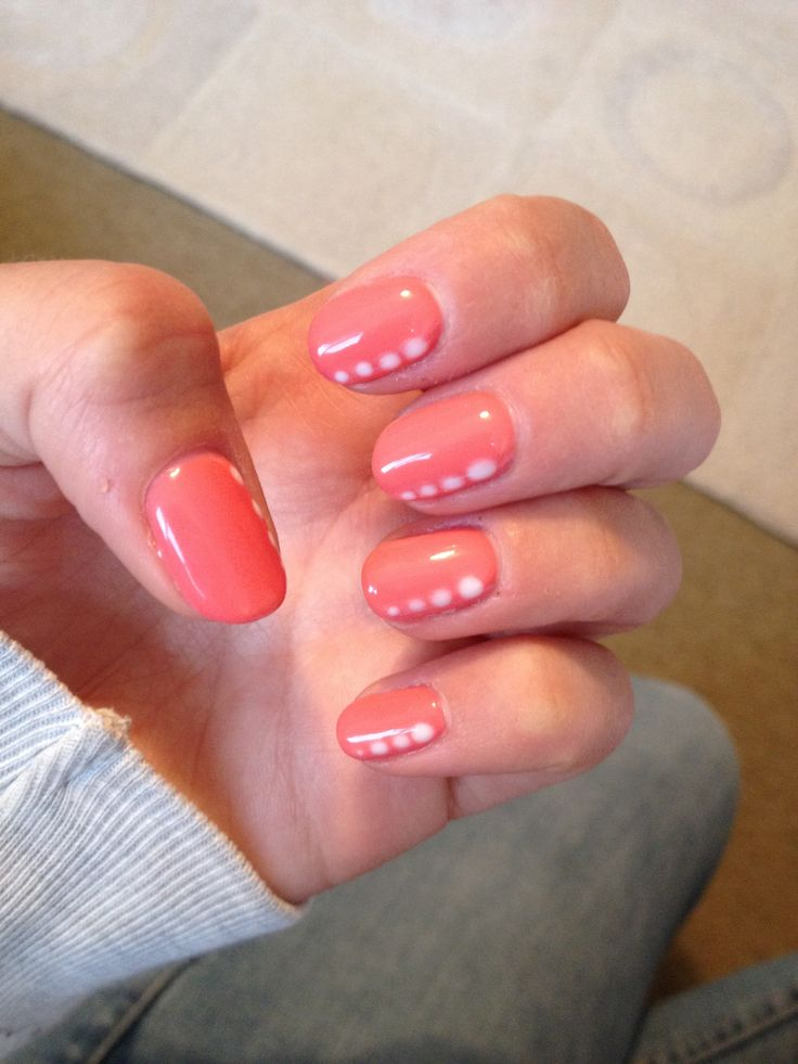 Coral gel nails with white nail art dots