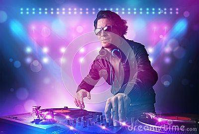 Disc jockey mixing music on turntables on stage with lights and by Ra2studio, via Dreamstime