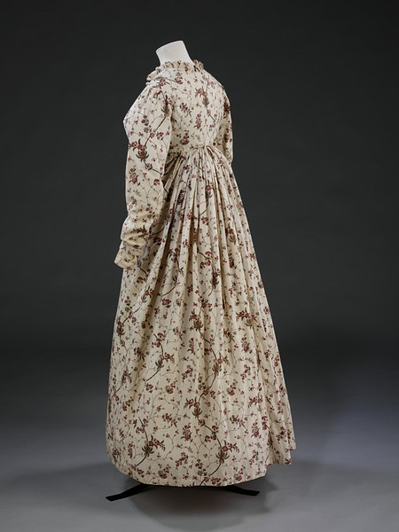 "Victoria  Albert Museum, item T.355-1980; 1795-99, block printed cotton. The dress is styled with a high-waisted , fitted bodice, which fastens centrally. The neck, which is trimmed with a 1"" frill of matching material, is rounded a the back and V-shaped at the front. The bodice is lined with white cotton which extends 1/3 of the way down the full length tapered sleeves."