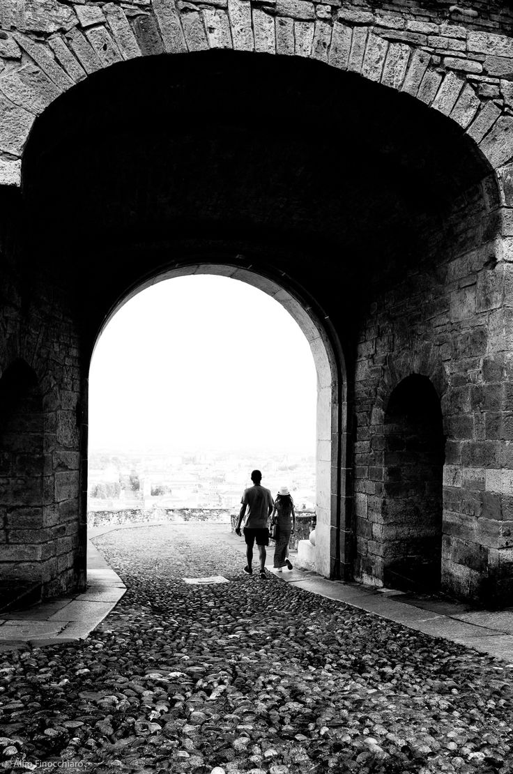 https://flic.kr/p/wMYnsW | Bergamo Alta | A young couple exiting from the antique arch door delitiming Bergamo Alta, Italy