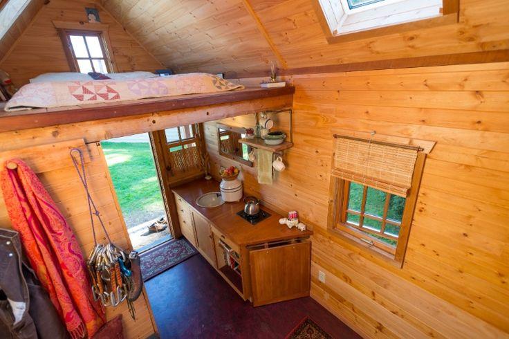 Pequena casa de 8m² no jardim, é moradia permanente de norte-americana. Deste ângulo é possível observar parte da casa, com a cama sobre o mezanino, a área da cozinha sobre a bancada e equipamentos de escalada e um lenço pendurados em frente ao armário (à esq.).  Fotografia: Stuart Isett / The New York Times / Casa e Decoração / UOL Mulher.