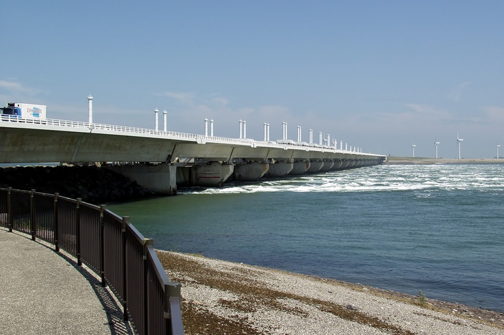 The Oosterscheldekering (in English: Eastern Scheldt storm surge barrier), between the islands Schouwen-Duiveland and Noord-Beveland, is the largest of the 13 ambitious Delta works series of dams, designed to protect the Netherlands from flooding. The construction of the Delta Works was in response to the North Sea Flood of 1953.
