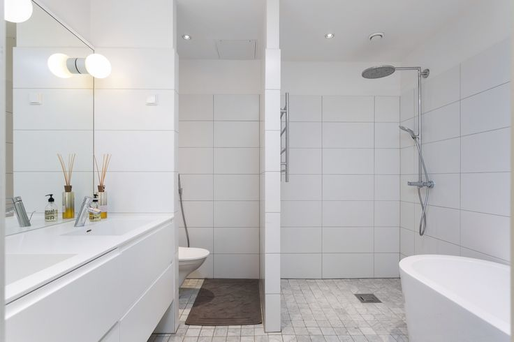 White bathroom, hans grohe , rain shower, white tiles, free standing bathtub, grey marble floor, lights in mirror,