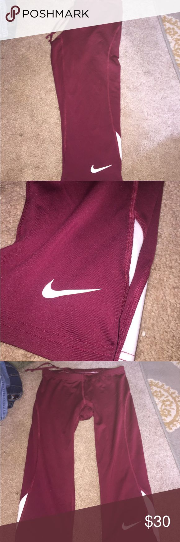 Nike running pants Disclaimer : Capri length Great condition. Maroon athletic pants wth white accents. Very minimal fraying Nike Pants Leggings