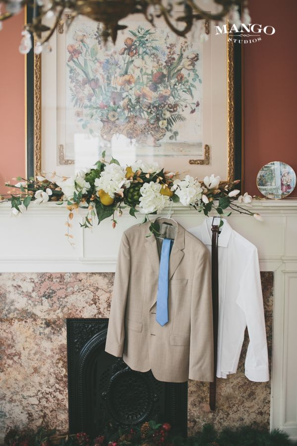 Waiting to be worn #weddings #groom #suit #tie #belt #shirt #fireplace #flowers #photography #mangostudios photography by Mango Studios