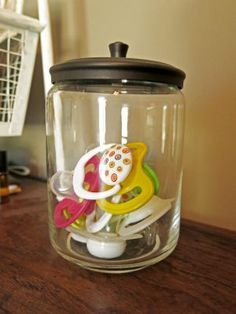 Keep your extra pacifiers in a glass jar with a lid on the dresser or changing table in your nursery. Keep them clean and handy! Nursery Storage | Nursery Organization | Rustic Woodland Nursery