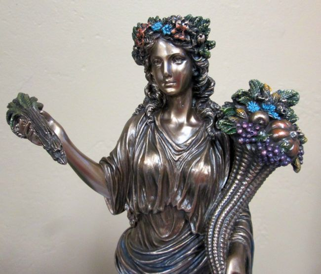 Demeter wears colorful flowers in her hair in this ...