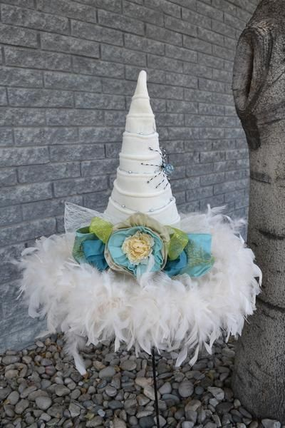 Be a cool and fresh witch this year in this cream colored hat dressed up in shades of blue and green. Cream Ridged Velvet19 inch brim; 19 inch tall.Adjustable