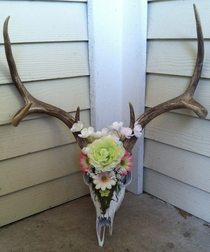Decorated old deer skull with moss and fabric flowers.