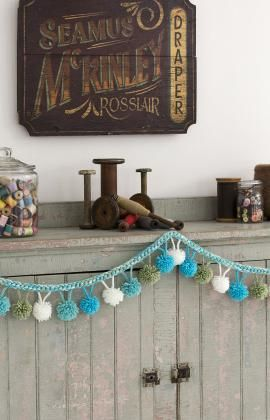 DIY home decor.  Crochet your own pompom garland to decorate your space from this free pattern.