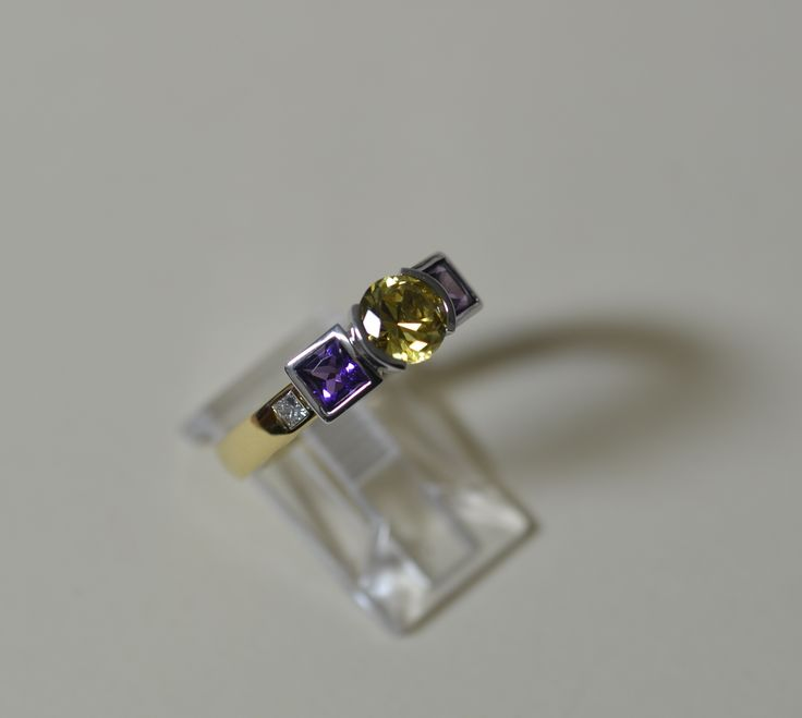 Yellow sapphire with amethyst and diamonds on the side.