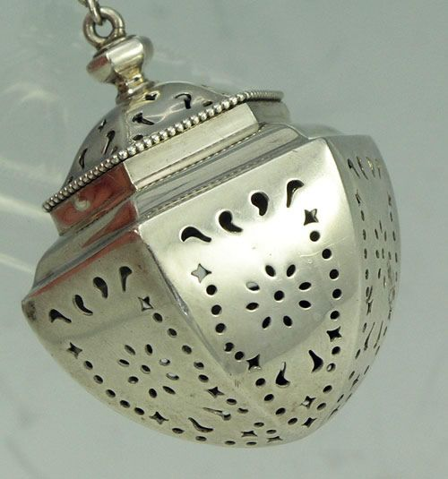 Gorham sterling tea ball with hinged lid and attached chain. The body is pierced and the lid has a granulated rim.