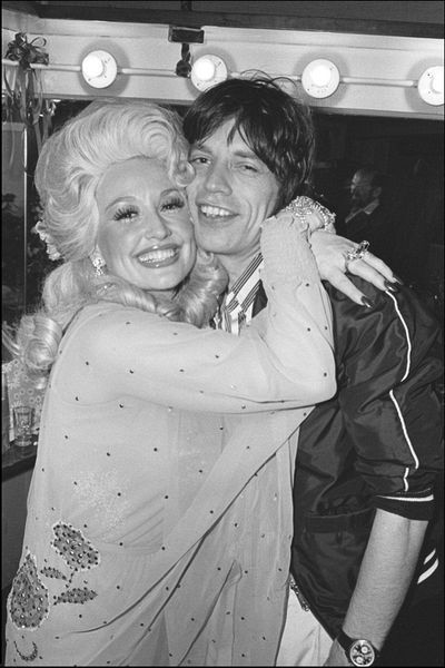 Dolly Parton hugs Mick Jagger backstage after her Bottom Line concert. 5/14/77 (Photo by Allan Tannenbaum)