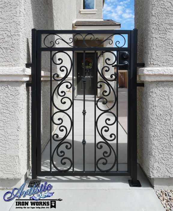 Wrought iron gate featuring scrolls and knuckles