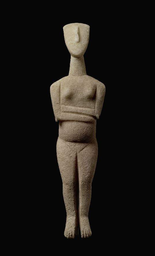 Cycladic marble figure of a goddess, Early Bronze Age II, 2600-2500 B.C. Of early Spedos type, lying with her arms folded above her pregnant belly, with grooved details in front and in back, and with slightly arched feet, sloping shoulders, tapering neck, and lyre-shaped head with convex facial plane, 27 cm high. Private collection