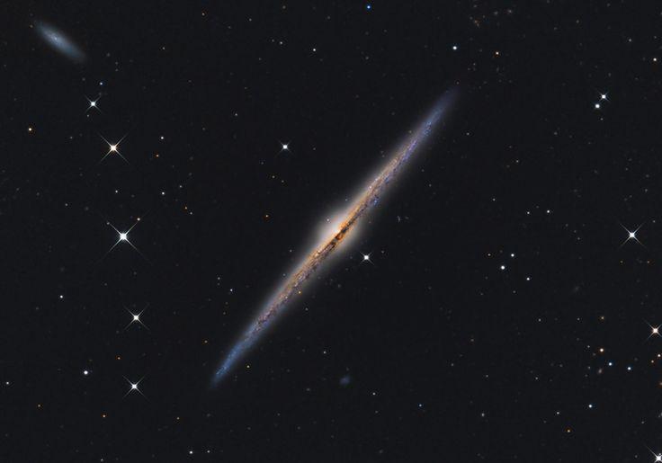 Галактика Игла (NGC 4565) в созвездии Волосы Вероники. Эта великолепная спиральная галактика расположена к нам ребром, поэтому мы не наблюдаем спиральных рукавов, зато очень хорошо видим центральное утолщение — балдж — и прослойку межзвездной пыли. Если бы мы могли взглянуть на нашу собственную звездную систему, Млечный Путь, со стороны, то она выглядила бы, вероятно, очень похоже на галактику Игла. Кроме NGC 4565 на снимок попало еще две галактики — NGC 4562 и IC 3571 (голубоватое…