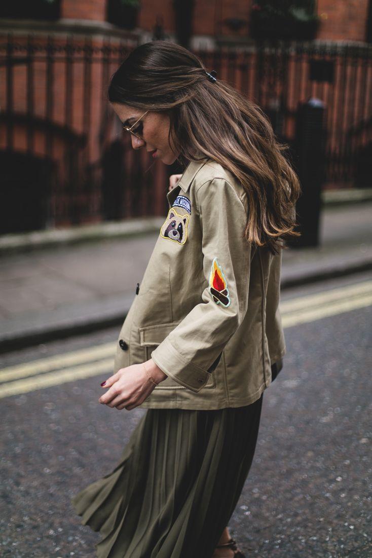 El fin de semana pasado estuvimos en Londres. Dos días intensos para vivir un trocito de su Semana de la Moda y en la que aproveché para llevar looks casual pero a la vez divertidos como este que os enseño hoy. El verde militar es uno de los colores clave de la temporada y combiné una falda plisada del tono con bolsillos y mucho vuelo con un chaqueta tipo trench con parches de Moschino. No puede gustarme más esa inspiración en las 'Girl Scouts'. Me recuerda a mi infancia en el colegio…