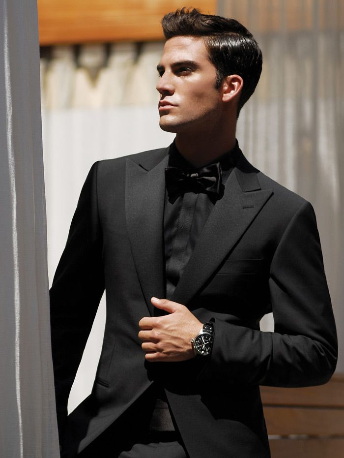 This is one clean tuxedo! Although it opts for high peak lapels instead of a shawl collar, it's all black shimmer and covered shirt placket make this tux the essence of clean and classic. Suit by: Ermenegildo Zegna.