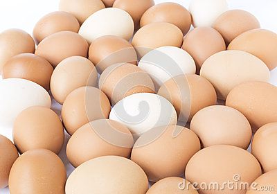 A large group of freshly laid brown and white organic chicken eggs.