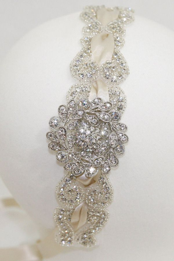 Vintage inspired headband contains beautiful crystals with a satin ribbon running through the headband. Stunning vintage jewel is placed on the side of the headband to help create a grand entrance on your big day. Design measures 1.75