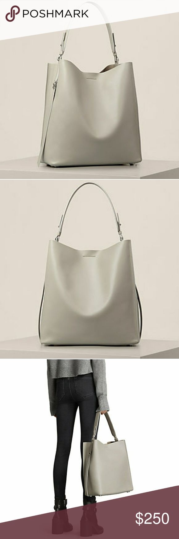ALLSAINTS Paradise North South Tote -Color: light cement grey -Single top handle -Magnetic Closure -Zip Pouch  -Interior slip pocket -Structured base with 4 protective metal feet -Smooth leather finish -Comes with allsaints dust bag and original tags 36cm-H, 34cm-W, 14cm-D, 22cm-Handle drop If interested in black please message, pricing will differ. No trades. All Saints Bags