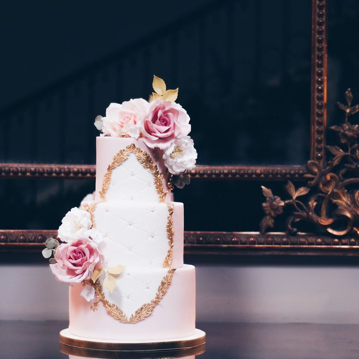 Here's a lavish rose adorned version of our Rococo-inspired wedding cake! Three blush pink tiers with a golden acanthus leaf frame and a quilted/tufted centre. Then our large bloom sugar roses (inspired by the Fifth Avenue and Quicksand varieties), hand-piped gold bees, small open white peonies, eucalyptus leaves, rose leaves, white damson blossoms, and golden berries! Delivered and set up at the beautiful @saltmarshehall! Congratulations Lauren & Liam! . Swipe left for more images! . Venue…
