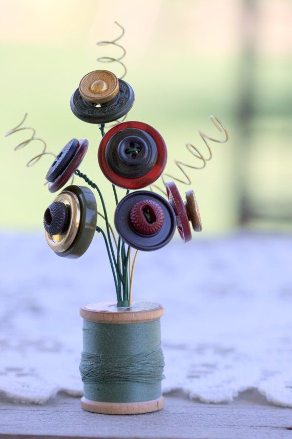 Buttons bouquet in wooden spool/So cute.  I have old thread spools that have beautiful thread on them, but the thread is to brittle to Sew with. Asw