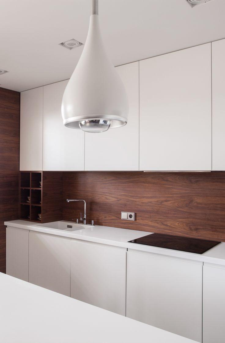 Nowoczesny, minimalistyczny design drewnianej kuchni, w której przeplata się biel szafek i ciemny brąz paneli ściennych i podłogowych     Modern, minimalist design of a wooden kitchen with white cupboards and dark brown wall and floor panels