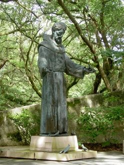 Saint Francis of Assisi with birds in a garden. Serene.