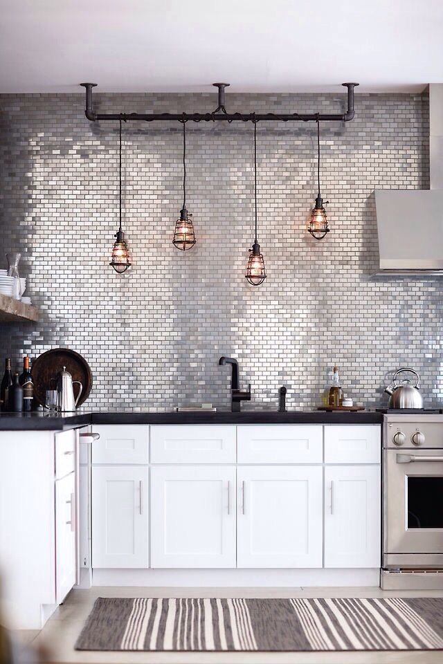 Vintage kitchen using metallic tiles and caged hanging lamps