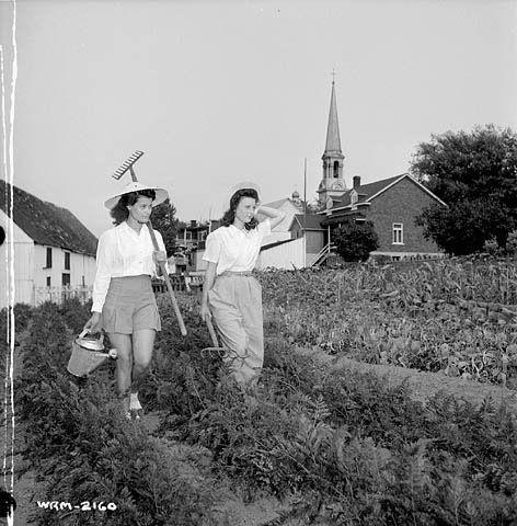 The Perry sisters, employed at the Dominion Arsenals Ltd. plant, armed with rake, watering can and pitchfork... / Munies d'un râteau, d'un arrosoir et d'une fourche, les sœurs Perry , employées à l'usine de la Dominion Arsenals Ltd. ... | by BiblioArchives / LibraryArchives