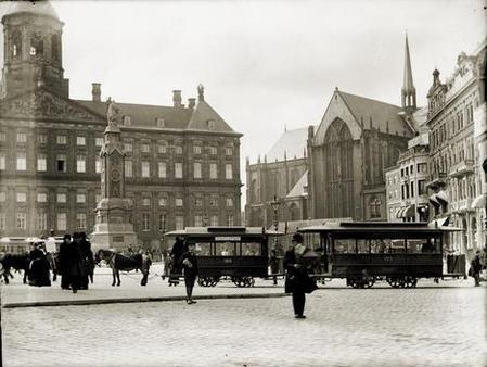 Op de achtergrond het Paleis en de Nieuwe Kerk. Links staat het standbeeld van Naatje op de Dam. Vooraan staan de paardentrams te wachten. 1896-1897