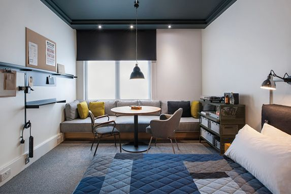 Ace Hotel (London) - Guest room configuration with long bench against the wall and small table.