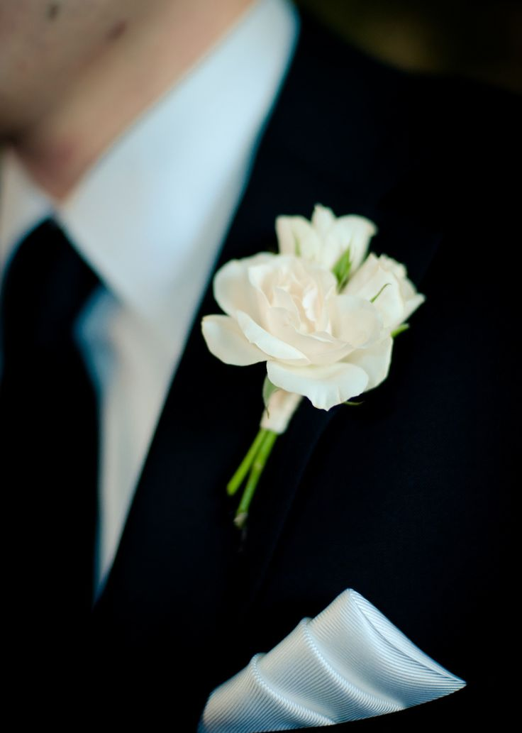 The men will wear boutonnieres of white spray roses and gray dusty miller wrapped in soft gold ribbon