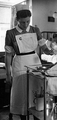 Ward nurse in traditional British uniform dress and startched white apron image…