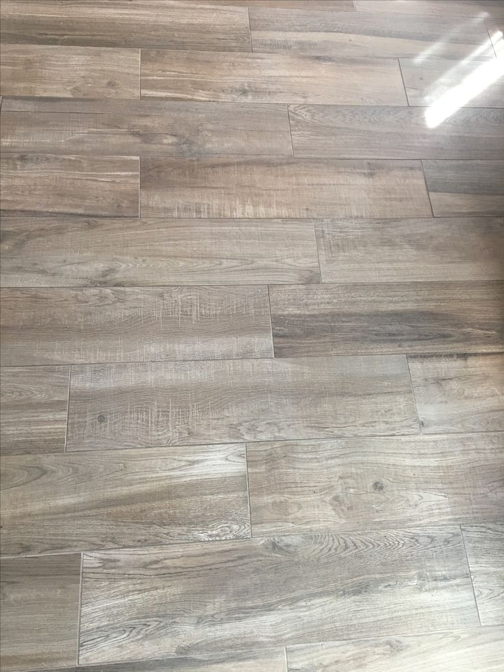 Wood look tile. Arizona Tile: Aequa Tur. Grout Color: Khaki. Coastal Farmhouse wood floors. Photo provided by Client of Matisse Realty