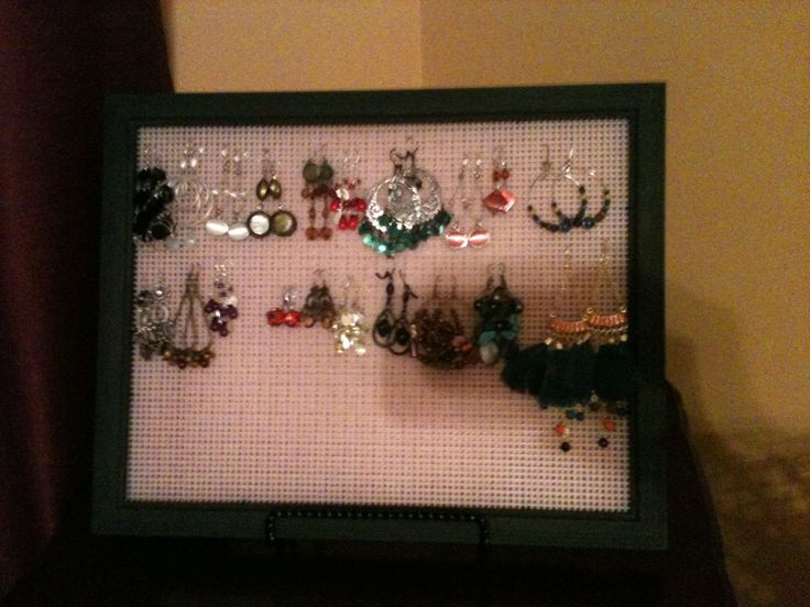 Homemade earring holder.  Plain frame painted.  Plastic mesh from Hobby Lobby's yarn sewing department.  Glued scrapbook chipboard on the back of the frame for support leaning room for French hooks.  Standing on an easel.  Maybe needs some embellishment in one corner what do you think?