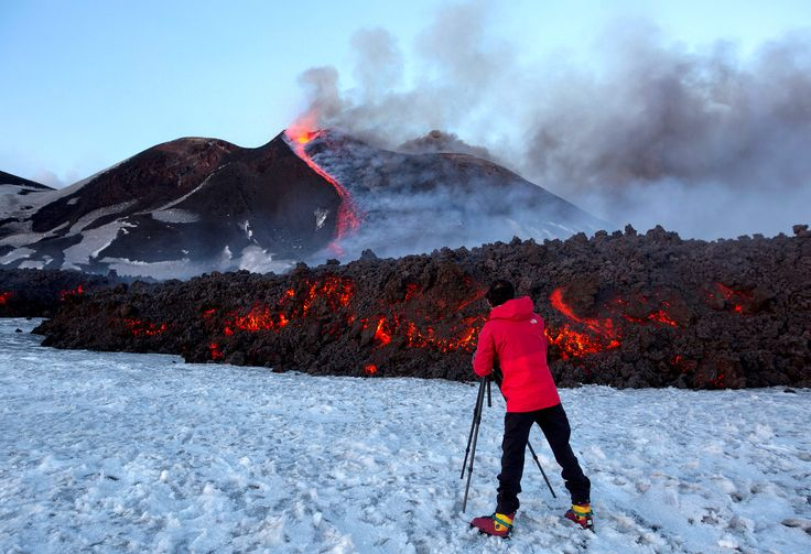 A tourist stands in front of Italy's Mount Etna, Europe's tallest and most active volcano, as it spews lava during an eruption on the southern island of Sicily, Italy, on February 28, 2017.
