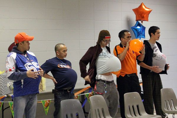 Great Baby shower game. Have volunteers blow up balloon and place under their shirts. They then sit down and tie their shoes to see who can do it the fastest without popping the balloon. Great fun!