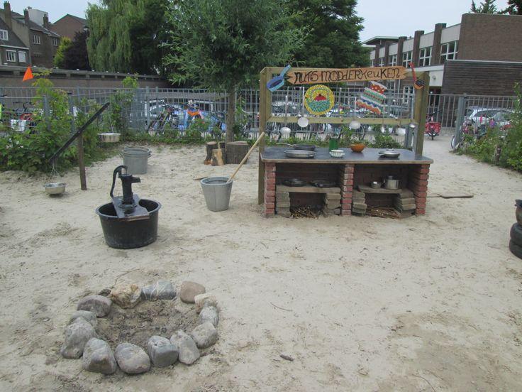 Een vuurplaats, de waterpomp, de reuzenvijzel en het keukenblok van de modderkeuken. Nutsschool Maastricht