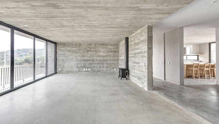 Casas Cuatas / Sala de concreto aparente, pisos de concreto pulido, aluminio gris europa y chimenea hergom