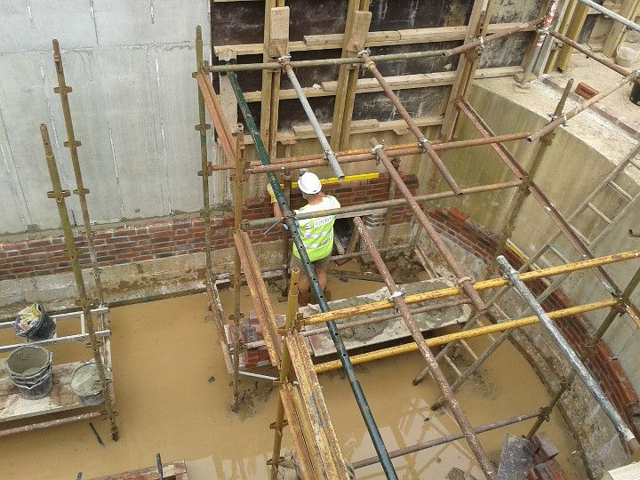 Construction of Gennets Bridge Lock. Bricklaying at the head of the lock. The shuttering in place above for casting the concrete for the paddle culverts.