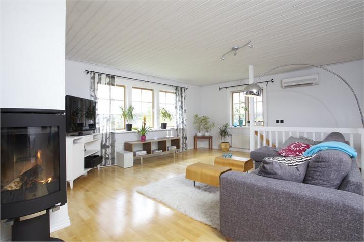 """Vardagsrum med kamin Jøtul F 363, lampa """"Sweep"""", soffbord IKEA –  Till salu: Vikene Solhagen, Brunskog, Arvika - Fastighetsbyrån"""