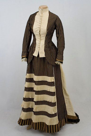 1870: The two-piece dress is fashioned primarily from a splendid striped fabric of bronze/gold corded silk and black velvet. The skirt hem, pleated ruffles, cuffs, and bustle back trim are of matching black and gold satin. The bodice front inserts, skirt front pleated ruffles, and sweeping back train are fashioned from ecru silk faille.