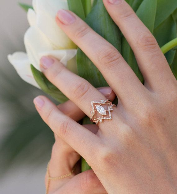 Our signature engagement ring, The Arrow Marquise features a floating center marquise diamond. The 14K gold band is thin and angular, feminine and strong. Center stone options below set with 42 pave diamonds and 4 bezel set round diamonds approximately .28 total carat weight without