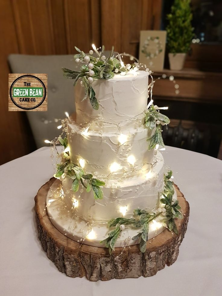 Rustic wedding cake creating romantic sparkle with fairy lights and mistletoe