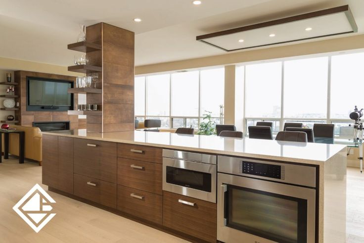 This modern kitchen features a lovely quartz countertop with a waterfall edge. Custom made sleek white cabinets to offset the warm chocolate brown cabinets.