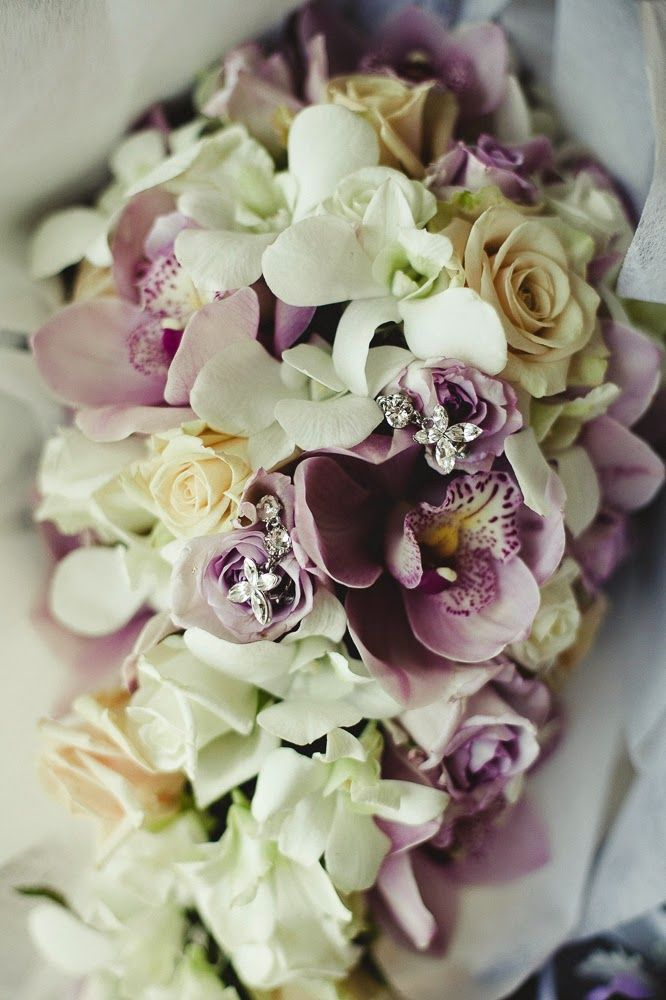 Delicate tear-drop wedding bouquet featured soft blooms, a mix of ivory roses, white and light purple orchids.