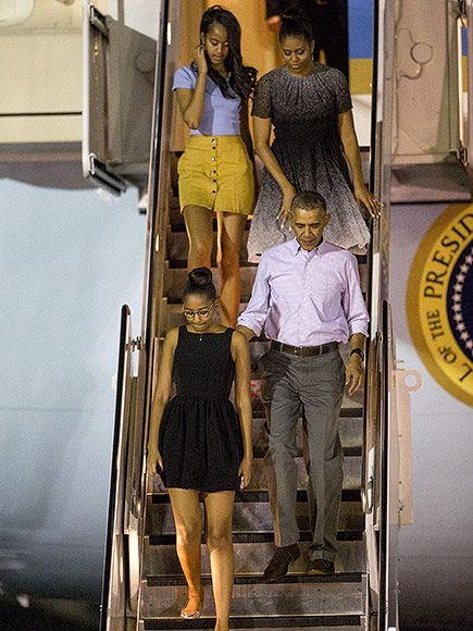 Michelle Obama wears a gray-and-black blended short-sleeved dress while touching down in Hawaii for the Obamas' Christmas vacation.